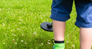 Boy searching a grass lawn with a metal detector